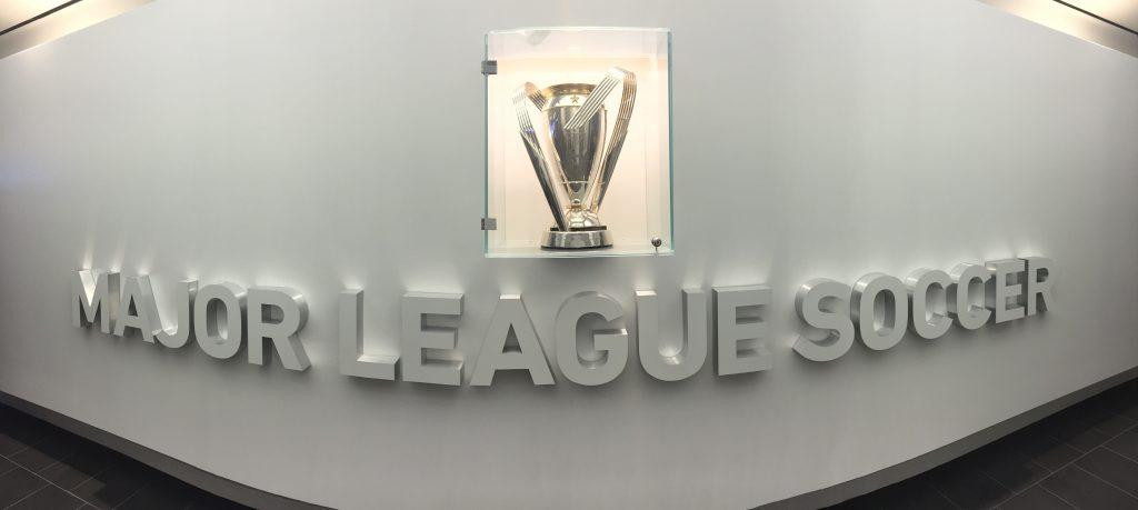 Primul lucru pe care-l vezi când intri în sediul din Manhattan al MLS este MLS Cup, trofeul suprem al campionatului nord-american de fotbal.